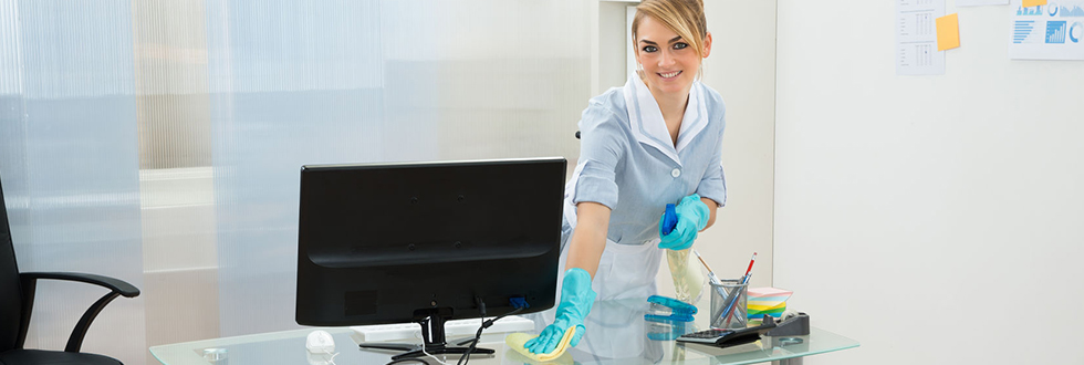 Blonde woman in a uniform looking directly at the camera whilst cleaning a desk in a pristine, white office