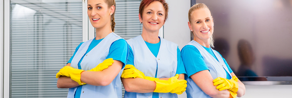 Three women in cleaning uniforms looking directly at the camera and smiling