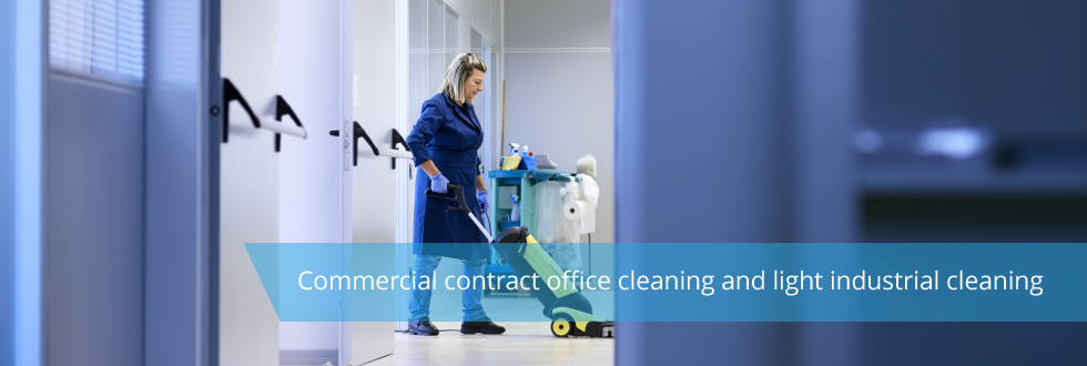 Long shot of a woman, in a commercial environment, hoovering with cleaning supplies behind her.